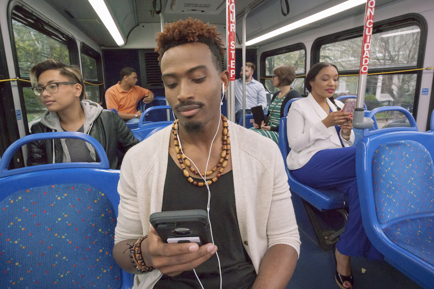 Bus riders shown seated inside bus, with primary focus on person shown using headphones while listening to something on their cell phone