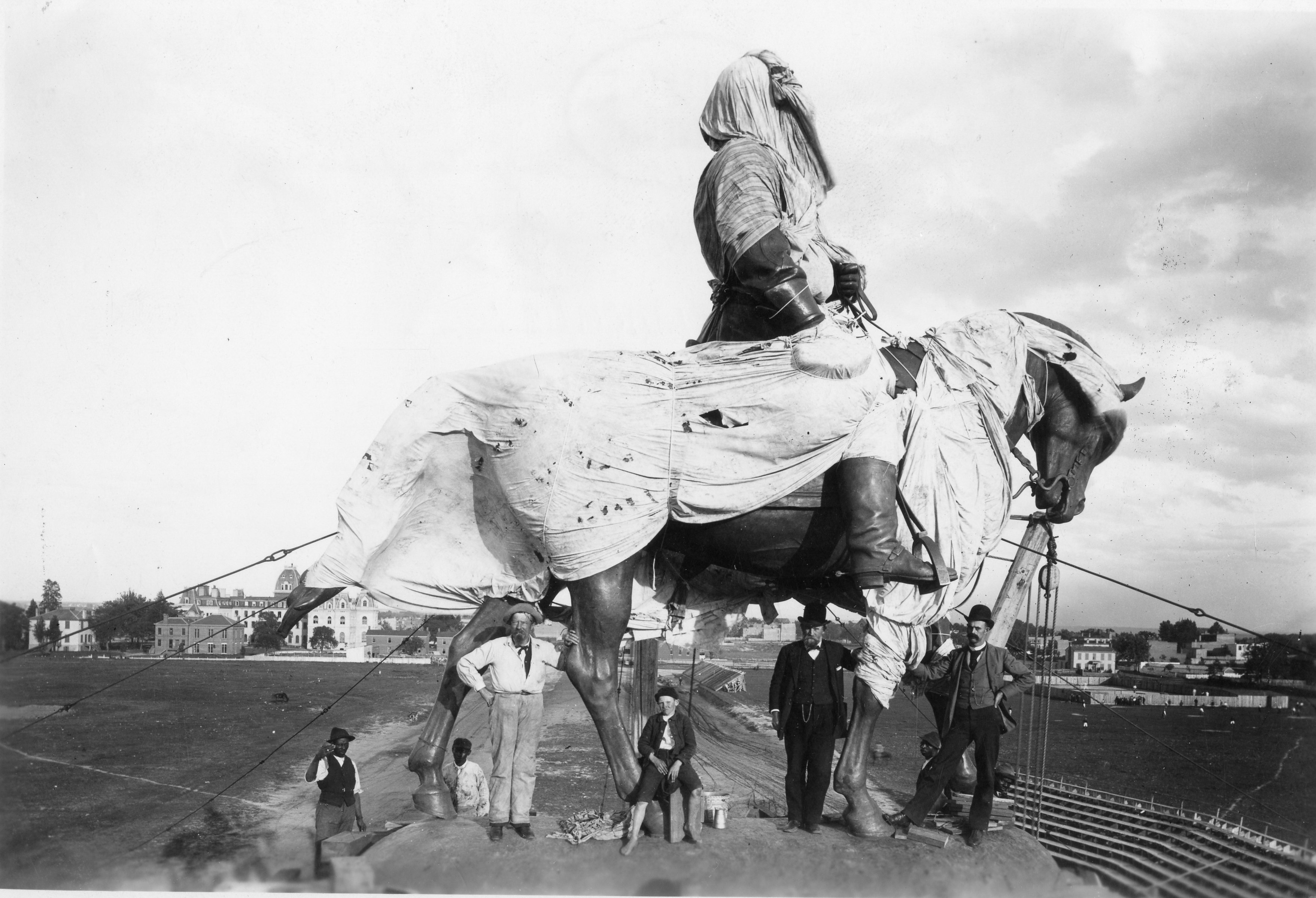 Workers on top of the Lee Monument, with the statue still wrapped and under construction prior to its unveiling